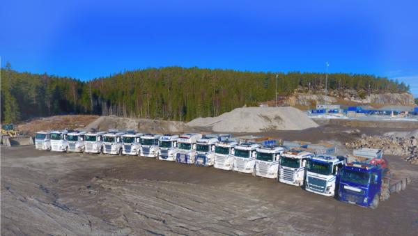 Hvite og blå lastebiler som står på rekke